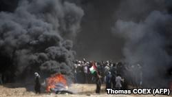 Një palestinez mban flamurin kombëtar, teksa tymi mbulon qiellin, gjatë përleshjeve mes palestinezëve dhe forcave izraelite në kufirin Gaza-Izrael. 14 maj, 2018