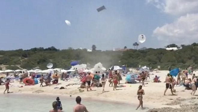 Era e fuqishme që përfshiu plazhin, ngriti në ajër dhjetëra çadra (Video)