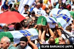 Disa persona bartin 33 trupat e identifikuar të Masakrës së Srebrenicës. Ata u varrosën në kompkeskin memorial në Potoçari. Bosnjë, 11 korrik, 2019.